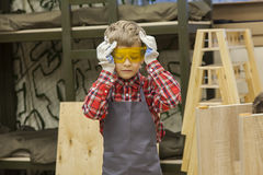 Young boy in work apron wearing protective goggles Royalty Free Stock Photo