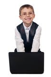 Young boy working with laptop. Portrait of a smiling young boy dressed up in suit sitting on the floor and working with laptop, isolated on white background Stock Images