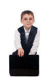 Young boy working with laptop. Portrait of a funny young boy dressed up in suit sitting on the floor and working with laptop, isolated on white background Stock Image