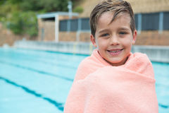 Young boy wrapped in towel standing at poolside Royalty Free Stock Photo