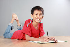 Young boy writing on the floor Royalty Free Stock Images