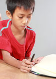 Young boy writing on the floor Stock Images