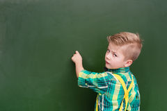 Young boy writing on a green chalkboard.  Royalty Free Stock Image