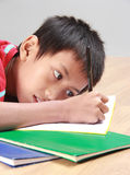 Young boy writing something on the book. Portrait of a stress young boy lay down writing something on the book Royalty Free Stock Images