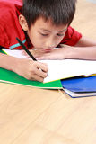 Young boy writing something on the book Stock Photo