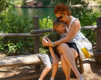 Boy Cries in Mother`s Arms. Young boy of 8 years falls and skins his knee. He is embraced and soothed by his mother as he cries from the surprise and pain after Royalty Free Stock Images