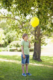 Young boy with yellow balloon at park Royalty Free Stock Photos