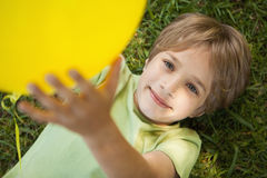 Young boy with yellow balloon at park Royalty Free Stock Photo