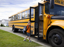 Young boy and yellow school bus. Young boy waves goodby while getting onto a yellow school bus royalty free stock image