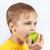 Young boy in yellow shirt eating a green apple Stock Photos