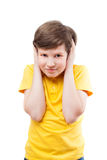 Young boy in yellow t-shirt shuts his ears by hands Stock Image