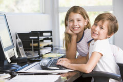 Young boy and young girl in office with computer Royalty Free Stock Images