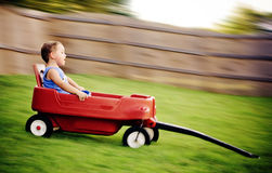 Young boy zooms downhill in wagon stock photo