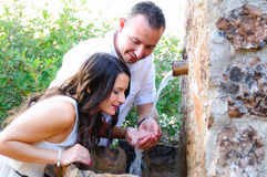 Young boyfriend giving drink to his girlfriend in a fountain Stock Photos