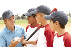 Young Boys In Baseball Team With Coach. Talking Stock Image