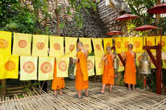 Young boys in Buddhist monastery decorated garden by flags with religious symbols Stock Image