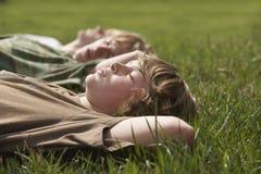 Young Boys détendant sur l'herbe Image stock