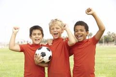 Young Boys dans la célébration d'équipe de football Images stock