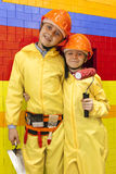 Young boys dressed like builders or workers. Two boys dressed in yellow overalls builders and hard hats Stock Photos