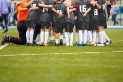 Young Boys en el fútbol Team With Coach del fútbol Charla B de la motivación Imagen de archivo