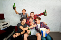 Young boys-fans watch TV, relax, have fun and drink beer. Friend Stock Image