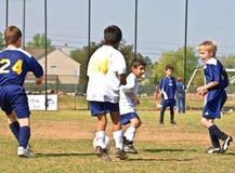 Young Boys-Fußball, der die Kugel beschmutzt Stockfotografie