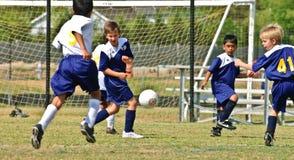 Young Boys-Fußball, der die Kugel beschmutzt Lizenzfreies Stockfoto