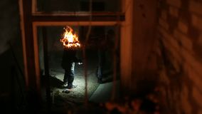 Young boys` gang playing by the fire at night. By the abandoned building stock video