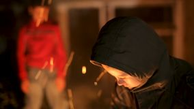 Young boys` gang playing by the fire at night. By the abandoned building stock video footage