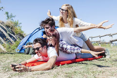 Young boys and girls in campsite. Piled up smiling stock image