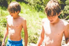 Young boys have fun at the small river stock photography