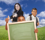 Young Boys Hold Blank Chalk Board with Teacher Outdoors Royalty Free Stock Photos