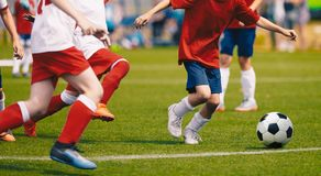 Free Young Boys In White And Red Soccer Jersey Shirts And Soccer Cleats Kicking Soccer Ball Stock Photo - 136834070