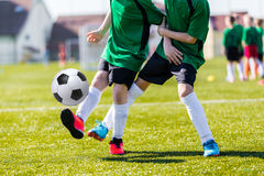 Young boys kicking soccer football on the sports field. Football match for children. Training and football soccer tournament Stock Photos
