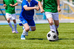 Young boys kicking soccer football on the sports field. Youth bl. Ue and green teams tournament competition Stock Image