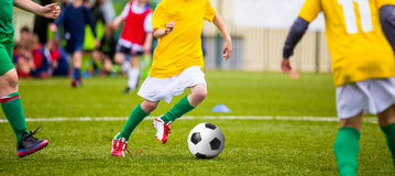 Young boys kicking soccer football on the sports field Stock Photo