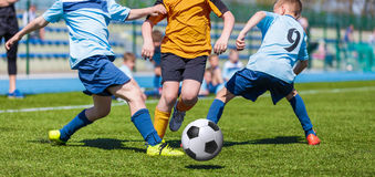 Young boys kids kicking soccer football on the sports field. Football match for children. Training and football soccer tournament Royalty Free Stock Images