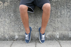 Young boys legs. Young boy sitting on a concrete wall Stock Images