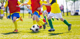 Young boys playing football soccer game. Kids kicking soccer ball on sports field. Youth european football teams playing soccer Royalty Free Stock Images