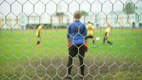 Young boys playing football soccer game. Running players in blue and yellow uniform stock footage