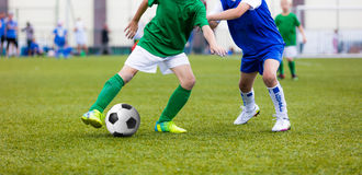 Young boys playing football soccer game on sports field. Running. Soccer players in sport shirts. Kids running and kicking soccer ball Stock Image