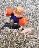 Young boys playing with pebbles at beach. A young boy covering his elder brother with pebbles on the beach Royalty Free Stock Photo