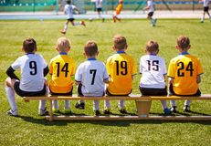 Young Boys Playing Tournament Soccer Match. Youth Soccer Club Footballers. Young Football Players. Young Soccer Team Sitting on Wooden Bench. Soccer Match For Stock Photos