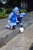 Young boys playing with toy boat in the rain 1 Royalty Free Stock Images