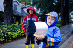 Young boys playing with toy boat in the rain 3 Stock Photos