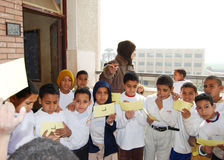 Young boys playing words game at school. Group of boys holding colored badges playing words game with female teacher at school building, at charity event, at a Royalty Free Stock Photography