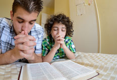 Young Family Praying. Young boys praying and praising God, Godly family exercising their faith at home Royalty Free Stock Photos