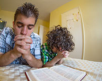 Young Family Praying. Young boys praying and praising God, Godly family exercising their faith at home Royalty Free Stock Images