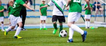 Young Boys que joga o fósforo de futebol do futebol no passo Crianças que correm com bola Imagens de Stock