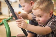Young Boys que juega en un tractor viejo afuera Imágenes de archivo libres de regalías